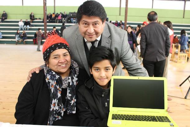 Director Eduardo Rosas al centro junto a alumno favorecido y su apoderada
