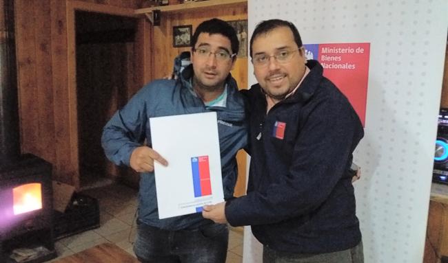 El presidente del Club Deportivo Asoden de Neltume, Cristian Valenzuela recibiendo el documento de manos del Seremi de Bienes Nacionales.