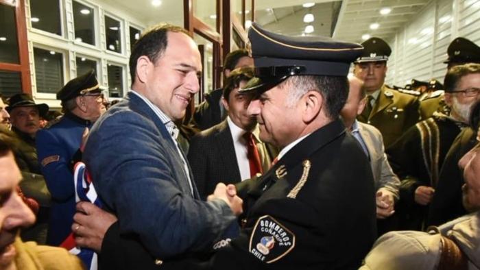 El abrazo entre el actual Intendente César Asenjo y el Director de la Compañía de Bomberos en Coñaripe, Roberto Martiní.